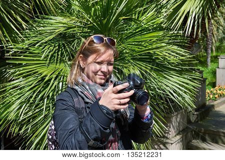 Woman Tourist Photographs In Park