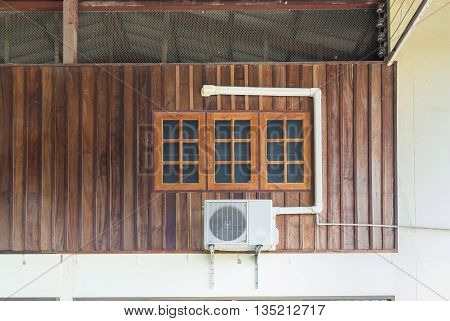 Air conditioning units installed outside the house on wooden wall