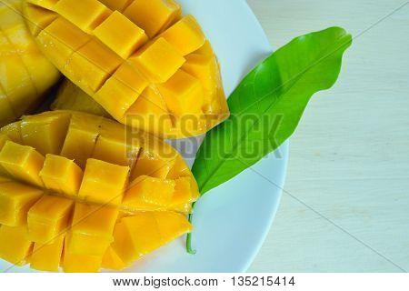 Mango nicely cut with leaf on plate (Other names of mango are horse mango Mangifera foetida Anacardiaceae Mangifera M. indica)
