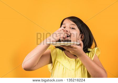 portrait of Indian kid eating cake or pastry, cute little girl eating cake, girl eating chocolate cake over colourful background