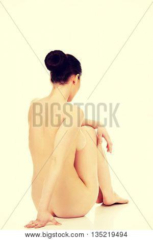 Naked woman sitting.