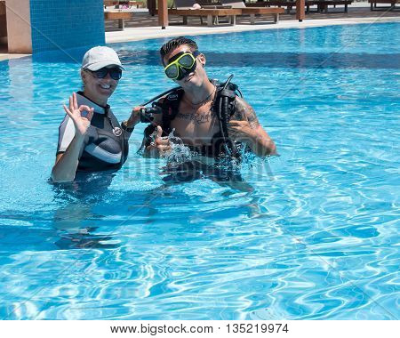 PaliouriGreece - June 15 2016: Young man tries a scuba dive in a pool with an instructor.Scuba diving is a fun sport enjoyed by many people.
