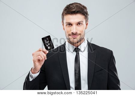 Portrait of handsome young businessman holding credit card over white background