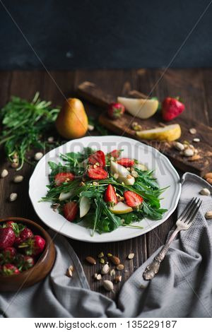 Healthy vegetarian salad with strawberry, arugula, pear and almond