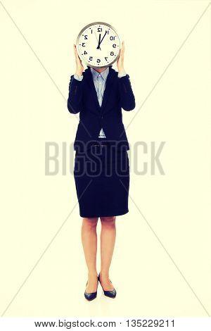 Business woman hiding behind big clock.