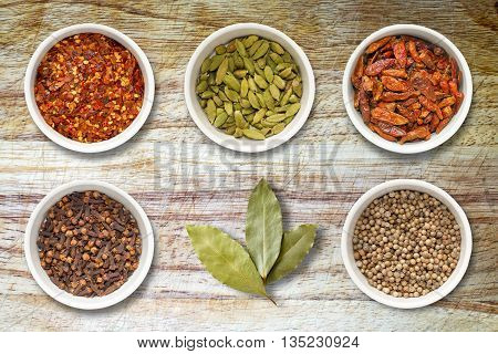 Spices including chilli flakes cloves bird's eye chillies cardamoms bay leaves and coriander seeds in white pots on an old scored wooden kitchen cutting board