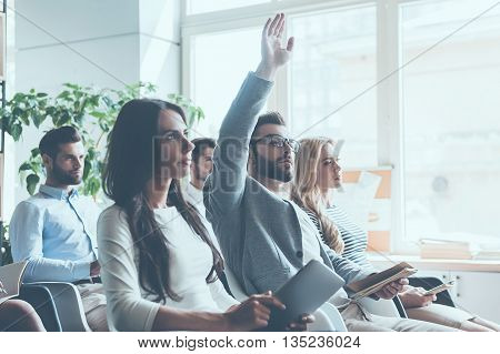 I have a question! Group of young people sitting on conference together while one man raising his hand