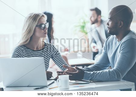 Discussing some business issues. Two young business people discussing something while sitting at the office desk together while their colleagues sitting in the background