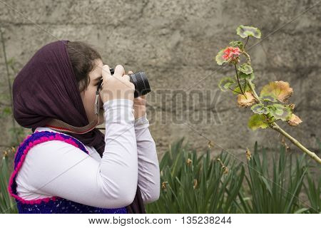 Young Little Girl Is Taking Photograph by an Analogue Camera Strapped on Her Neck in Flower Garden