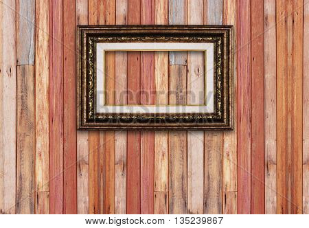 Gold picture frame isolated on wood background.