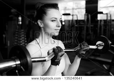 Young beautiful woman doing biceps curl with EZ curl bar in a gym. Athletic girl doing workout in a fitness center poster