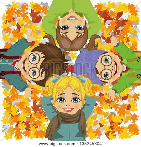 happy kids lying on colorful autumn leaves in the park