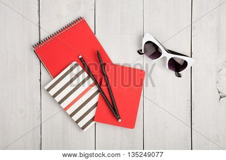 Desktop With Red And Strip Notepads, Pensils, Sunglasses On A White Wooden Desk