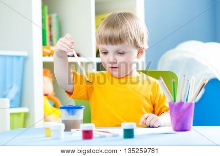 kid boy playing and painting at home or kindergarten or playschool
