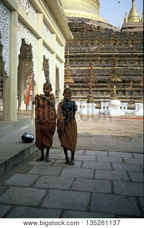 PAGAN / MYANMAR - CIRCA 1987: Two young novice monks with begging bowls at the Shwezigon Pagoda in Pagan.