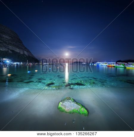 Night landscape at the sea with stone yellow sand and lunar path. Moonrise. Travel background