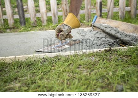 Low angle closeup view of a man with protective gloves leveling the surface of a concrete plate outside in back or front yard.