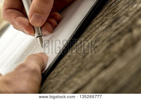 Low angle closeup view of male hand signing contract document or application form with a pen on textured wooden desk.