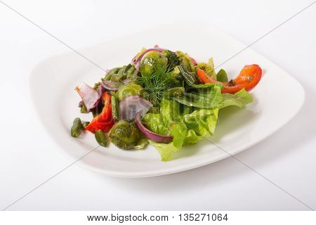 Mixed green vegetables salad served on a white plate