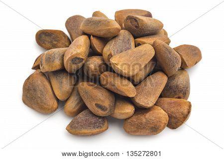 Pile of unpeeled cedar nuts on white background. Siberian cedar seeds, Pinus sibirica.