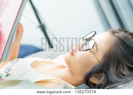 Asian Eyeglasses Lovely Cute Women Reading Book On Bed At Home