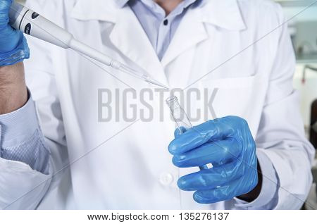 Caucasian male chemist scientific researcher in medical mask blue rubber gloves and white coat using test tubescultivating whit inoculation loops in pipette at his workplace in the laboratory.