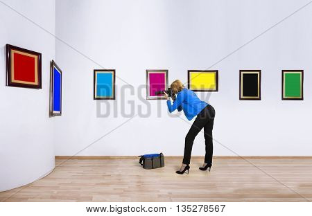 Female photographer reporter shooting at blank of CMYK and RGB color frames in art gallery.