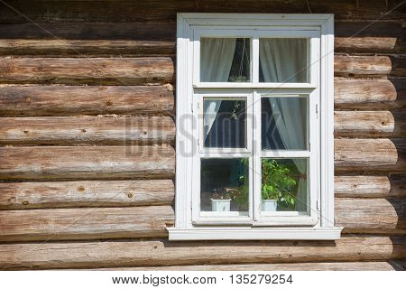 Window on old wooden facade of Russian town
