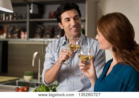 Happy young couple drinking white wine after cooking. Friend drinking wine in kitchen before dinner. Friends raising toast. Toasting between friends at home.