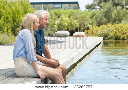 Romantic senior couple with the feet in the pool. Happy mature couple relaxing and holding hands outdoors. Happy senior couple enjoying vacation near pool side with feet in the pool.