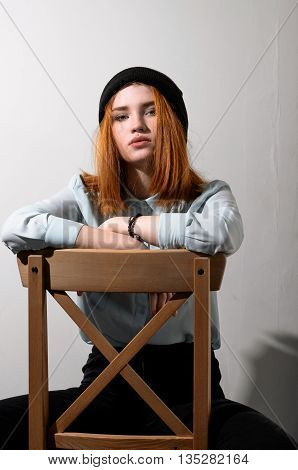 Red-haired Girl Sitting On A Chair.