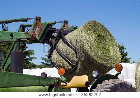 agriculture machinery handler picking up hay roll