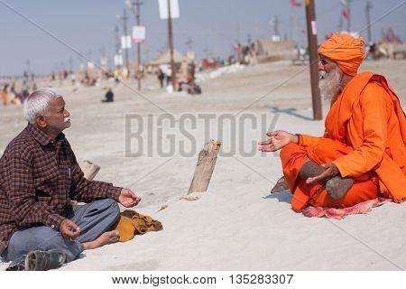 ALLAHABAD, INDIA - JANUARY 26, 2013: Holy hindu man Sadhu talks with indian senior about god during the festival Kumbh Mela on January 26, 2013 in Allahabad. In 2013 Kumbh Mela taking 130 000000 people