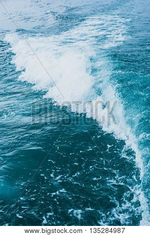 Abstract background texture of waves on blue sea behind the speed boat.