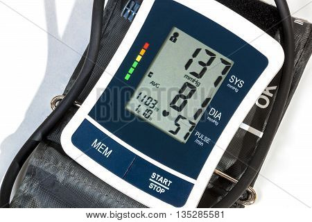 Close up right side view of blood pressure monitor cuff and pipe on over white