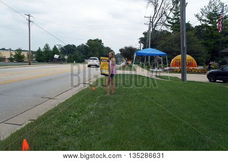 SHOREWOOD, ILLINOIS / UNITED STATES - AUGUST 30, 2015: A girl holds a sign to advertise a car wash as a fund raising activity on Jefferson Street in Shorewood.