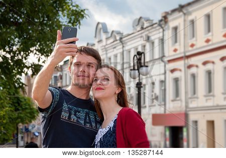 girl and boy Make selfie photos on a city street