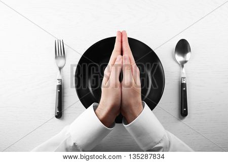 Man holding hands over empty plate. Hunger concept