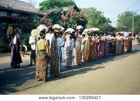 PAGAN / MYANMAR - CIRCA 1987: Women in beautiful dresses march together, some bearing pots on their heads, in a Buddhist parade in Pagan during a holiday.