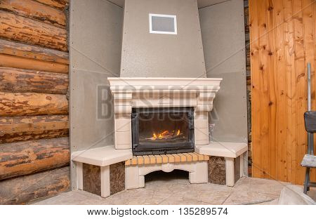 Unfinished burning fireplace in a wooden house