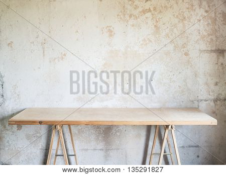 Wooden workshop table against concrete wall.