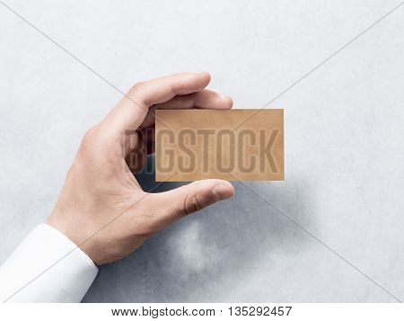 Hand hold blank plain kraft business card design mockup. Clear calling card mock up template holding arm. Visit pasteboard craft paper display front. Small offset texture card print. Business identity