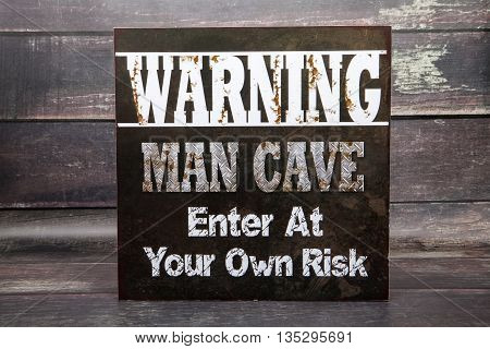 A man cave novelty sign against a wood background