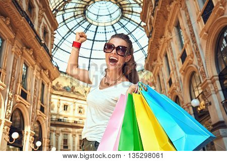 Discover most unexpected trends in Milan. Happy fashion woman in eyeglasses with colorful shopping bags in Galleria Vittorio Emanuele II rejoicing