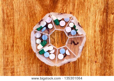Open pillbox full of pills divided on daily doses