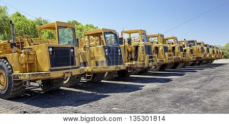 Heavy equipment tractor scrapers for road building and construction