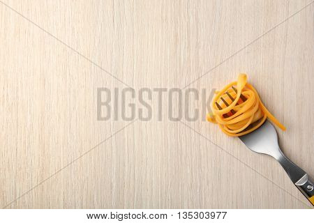 Fork with cooked pasta on wooden background