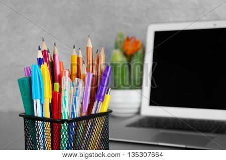 Colorful pencils and pens in metal holder, close up