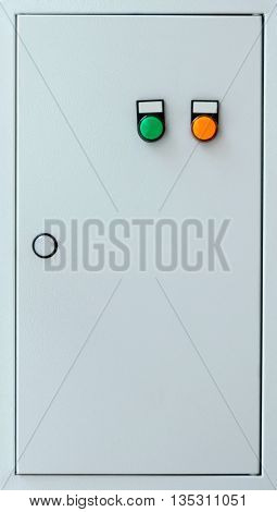 Grey colored door of the electric cabinet with the green and orange buttons.