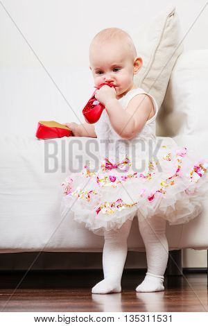Infant in time of teething. Sweet cute baby girl biting chewing red shoe. Young adorable child wearing white princess dress.